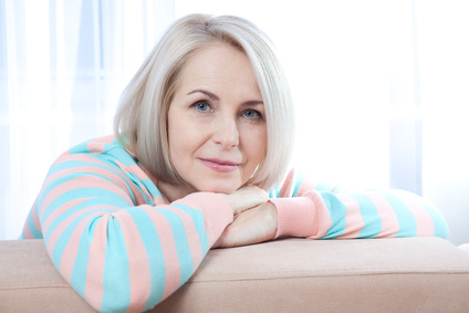 Attractive middle aged woman looking in camera relaxing at home. The beautiful face close up.
